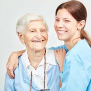 Krankenpflegehelfer für Senioreneinrichtung in Magdeburg betreut lächelnde Seniorin