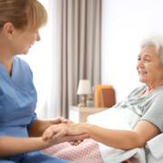 Krankenpfleger der PROMIND medical in Magdeburg betreut lächelnde Patientin
